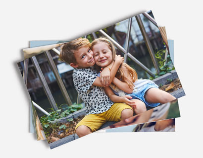 pile of photos with top photo showing boy and girl embracing