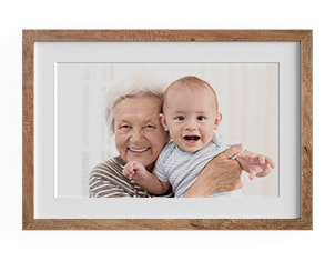 photo in wooden frame showing elderly woman holding baby