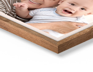 corner of photo in wooden frame showing elderly woman holding baby
