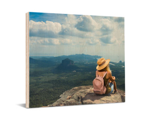 wooden print showing photo of woman sitting on cliff edge