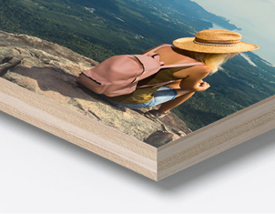 corner of wooden print showing photo of woman sitting on cliff edge